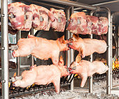 Carcasses of pork and other meat prepared on skewer.