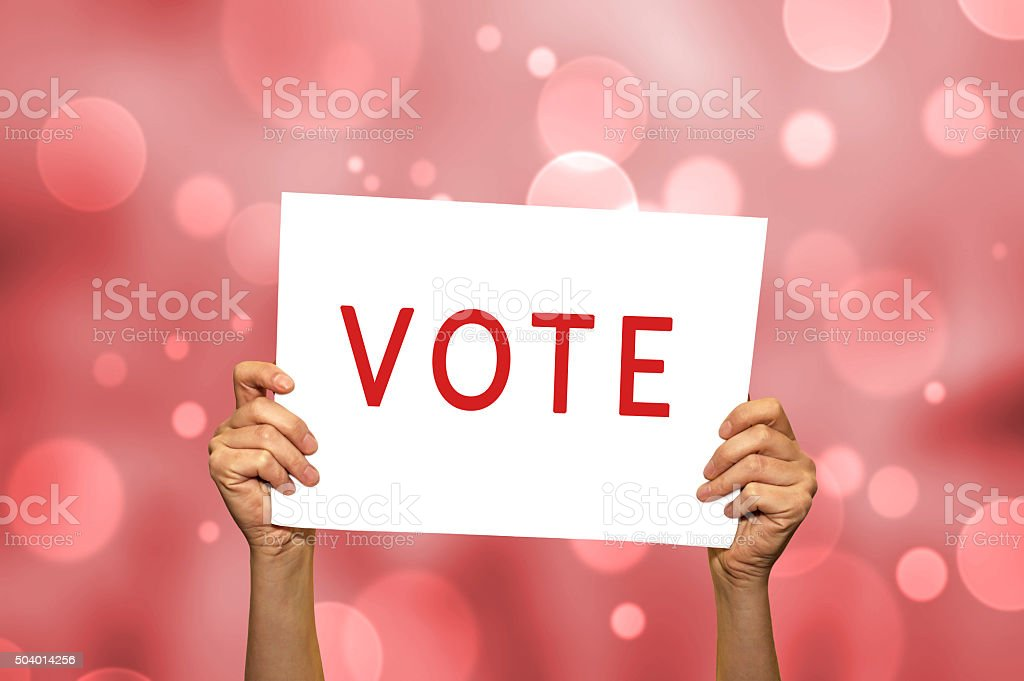VOTE card in hand with abstract light background. stock photo