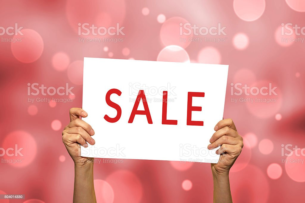 SALE card in hand with abstract light background. stock photo