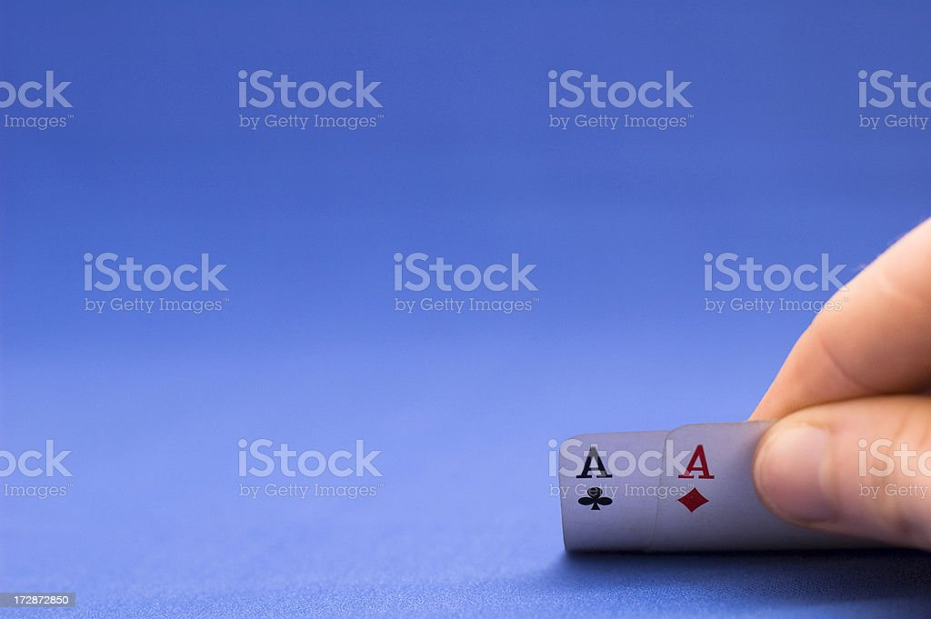 Card Player Shows Pocket Aces Against A Blue Background stock photo