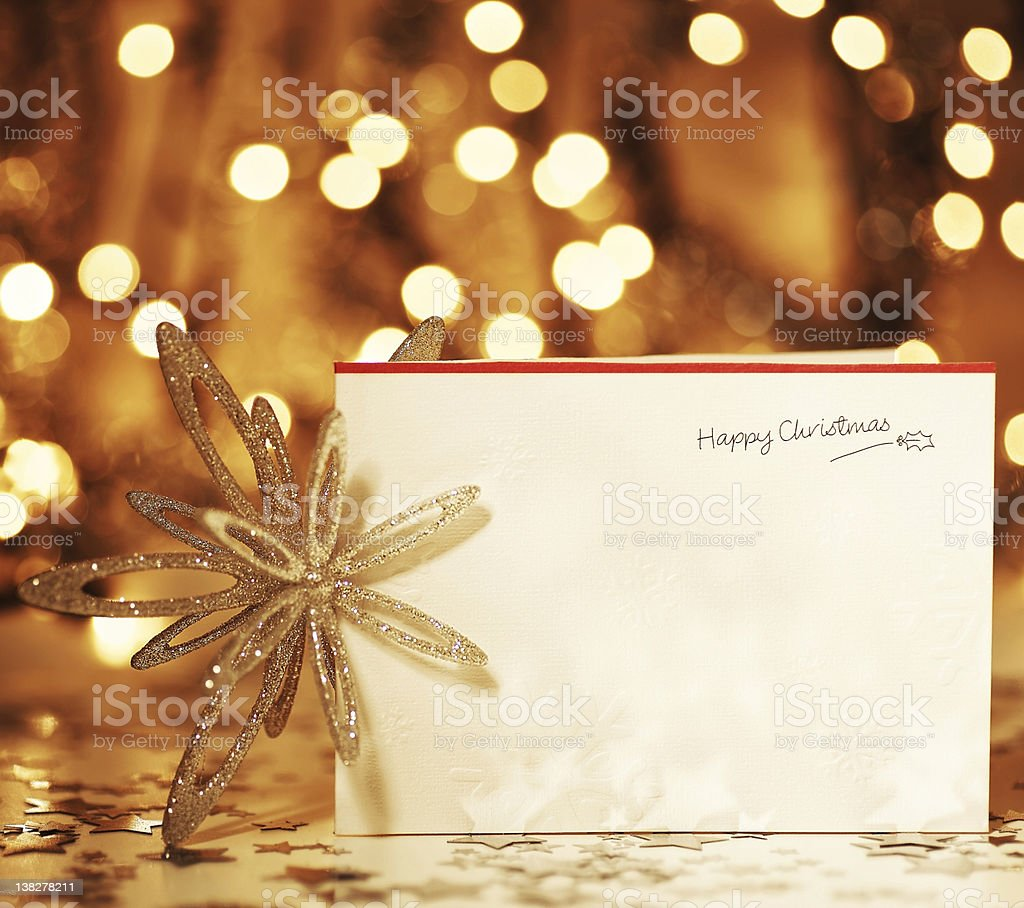 A card that reads happy Christmas in front of lights stock photo