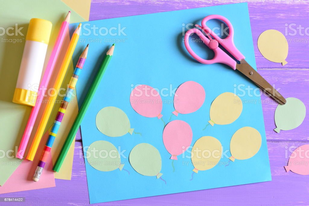 Card with paper air balloons, scissors, glue stick, colored paper, pencils on a table stock photo