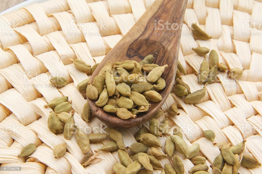 Cardamom berries in the wooden made spoon stock photo