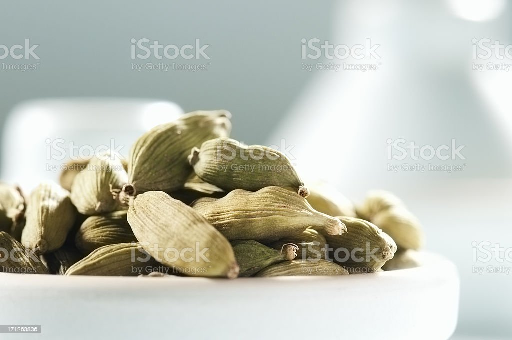 Cardamom pods in a small bowl with a blue background royalty-free stock photo