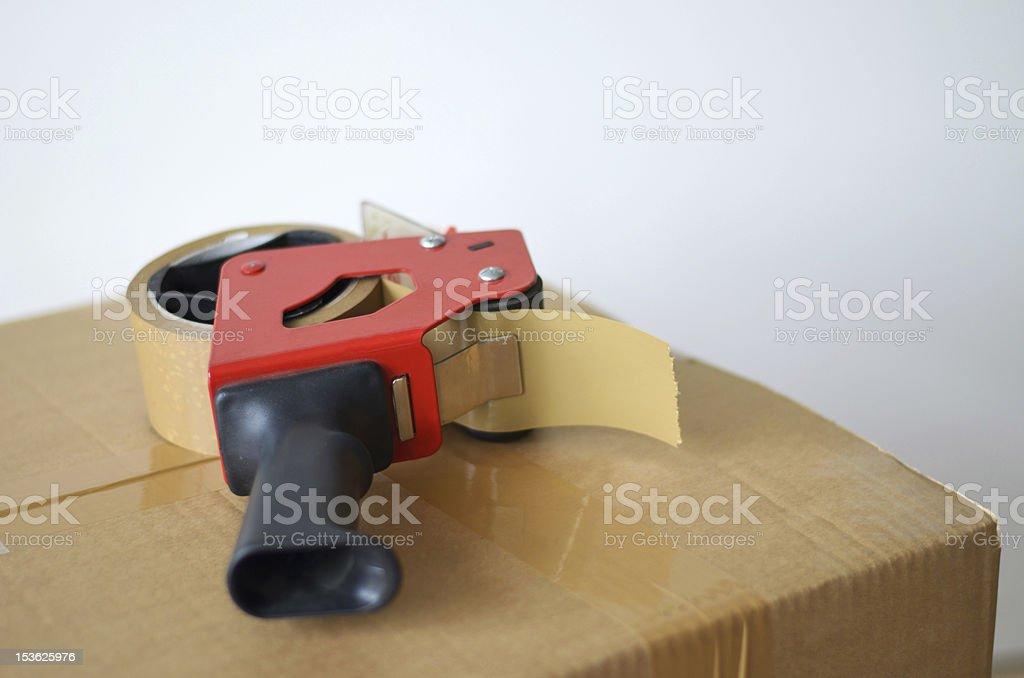 Cardboard box and tape dispenser stock photo