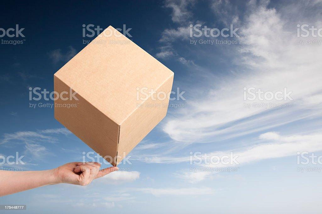 Cardboard box balancing on fingertip royalty-free stock photo