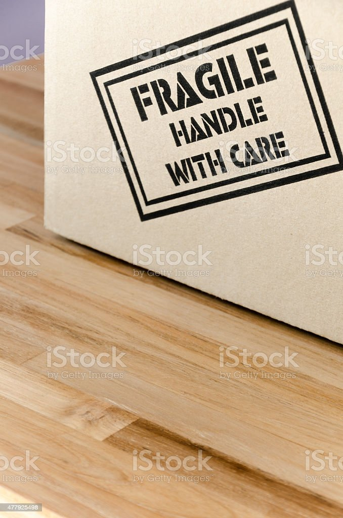 Cardboard box labelled \'Fragile handle with care\' on a wooden table