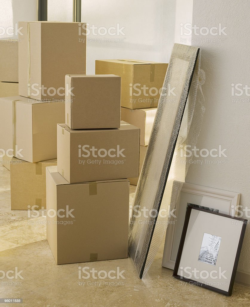 Cardboard boxes and pictures in new house stock photo