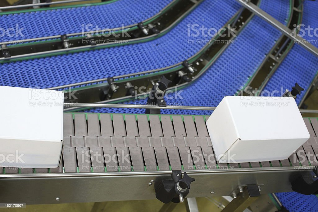 Cardboard boxes on conveyor belt in plant stock photo