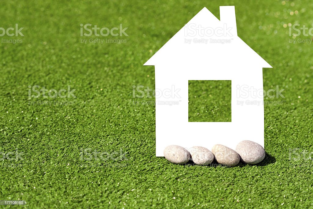 cardboard house with stones against the green grass royalty-free stock photo