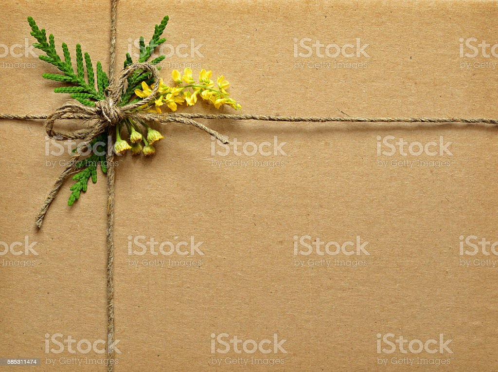 Cardboard tied with small wild flowers bouquet and rope stock photo
