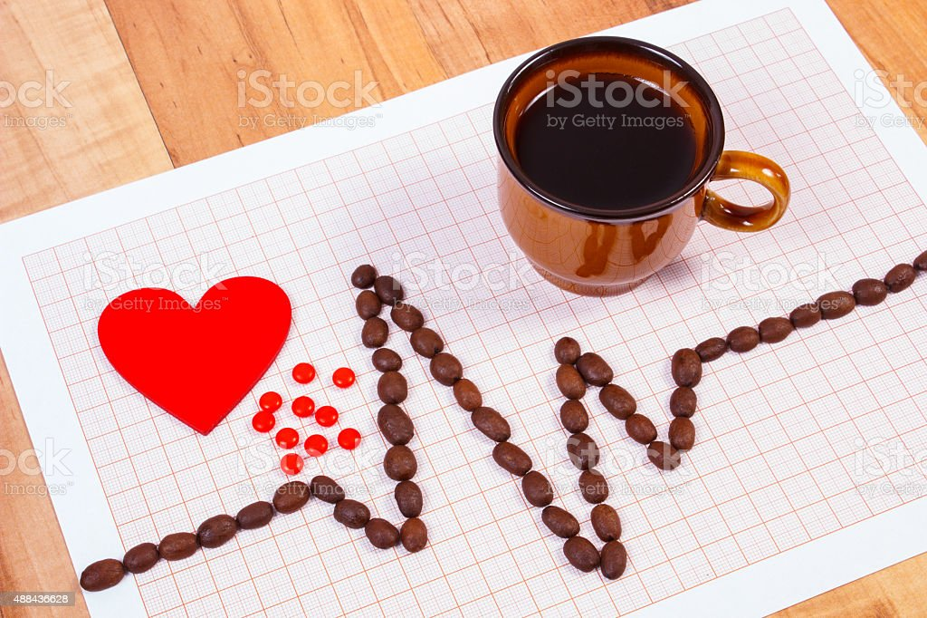 Cardiogram line of coffee grains, cup of coffee, supplement pills stock photo