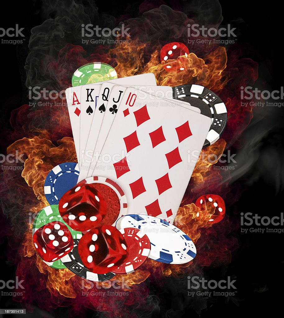 Cards sitting on poker chips and dice with flame background stock photo