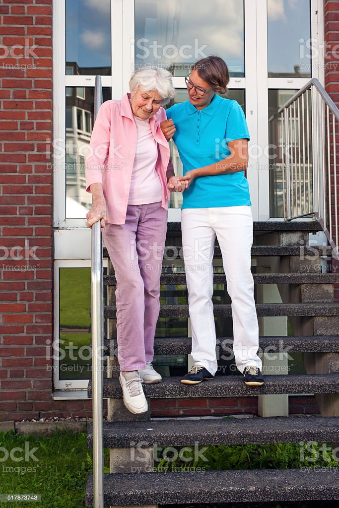 Care assistant helping a senior lady on steps. stock photo