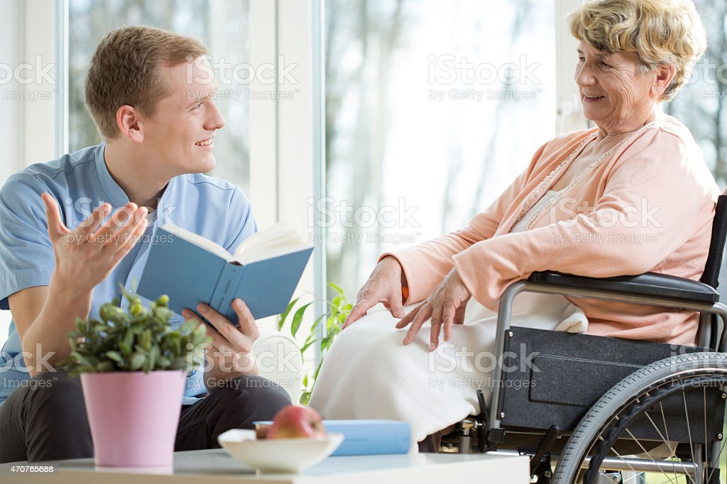 Care assistant reading book stock photo