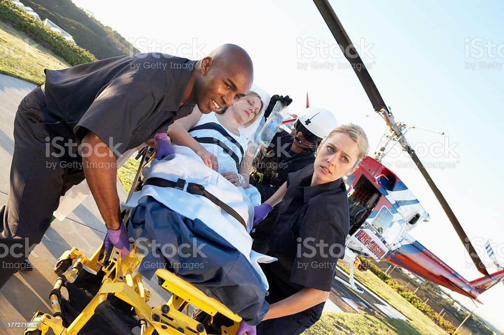 Care flight paramedics take woman out on a stretcher stock photo