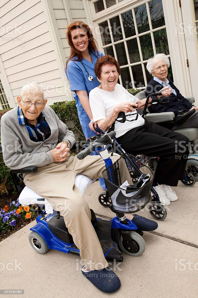 Care Nurse Helping Group of Senior Adults on Motorized Carts royalty-free stock photo