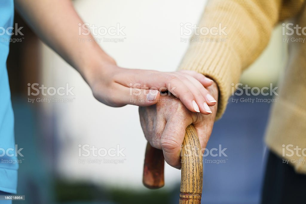 Care provider holding senior patient's hand stock photo