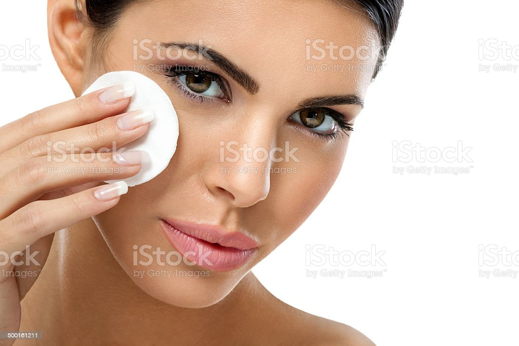 care woman removing face makeup with cotton pad stock photo