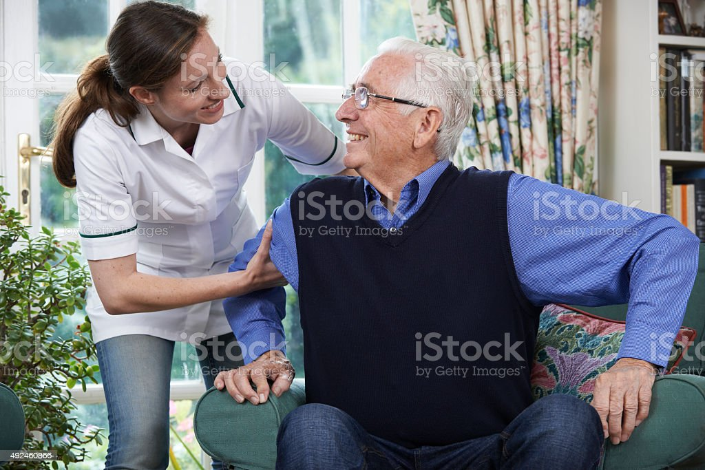 Care Worker Helping Senior Man To Get Up stock photo
