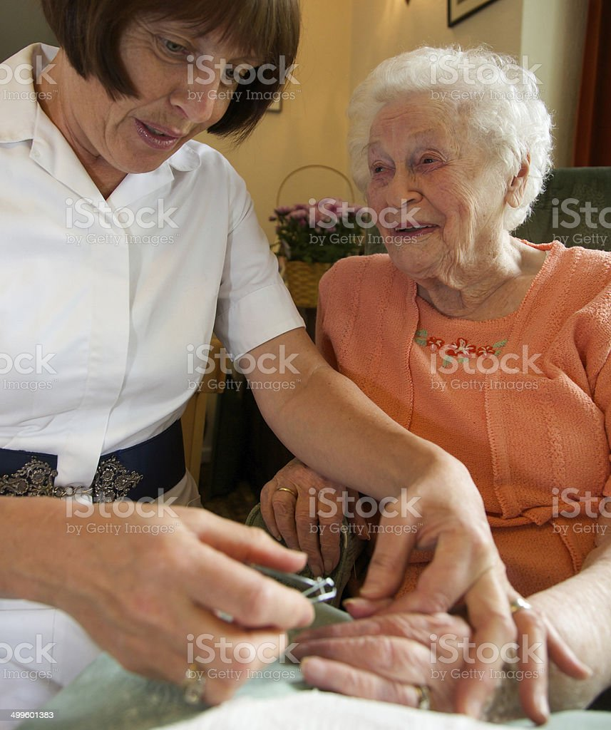 Care worker nurse caring for an elderly woman stock photo