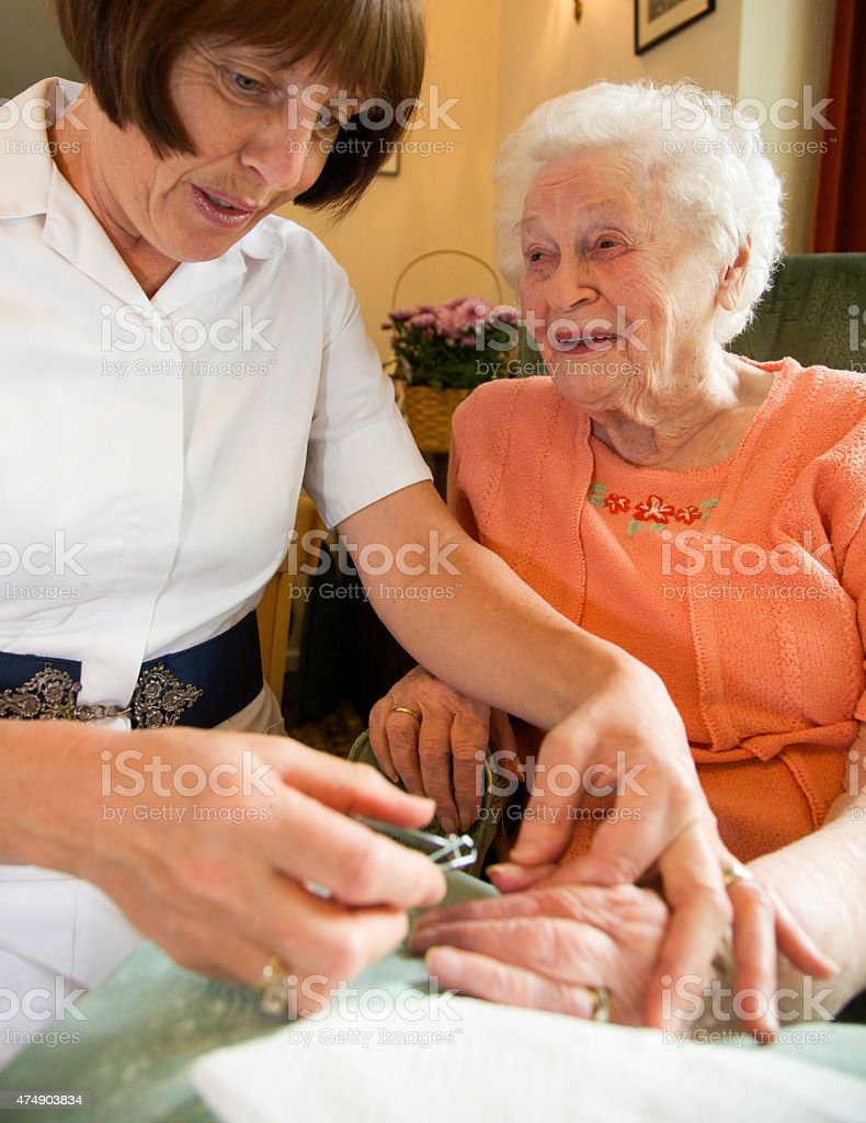 Care worker nurse caring for an elderly womans nails. stock photo