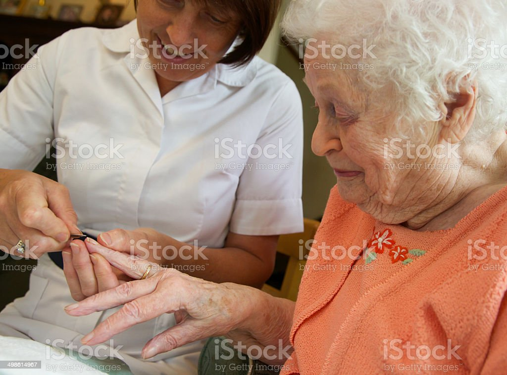 Care worker nurse caring for an elderly woman's nails stock photo