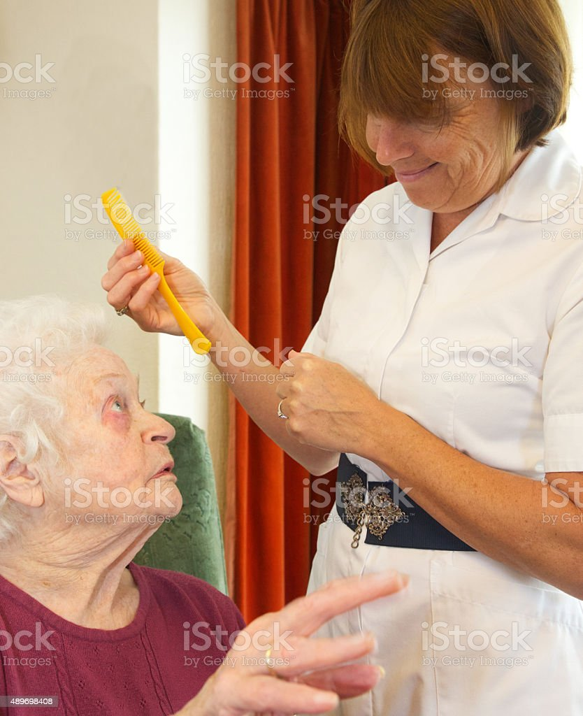 Care worker nurse helping an elderly woman with her hair stock photo