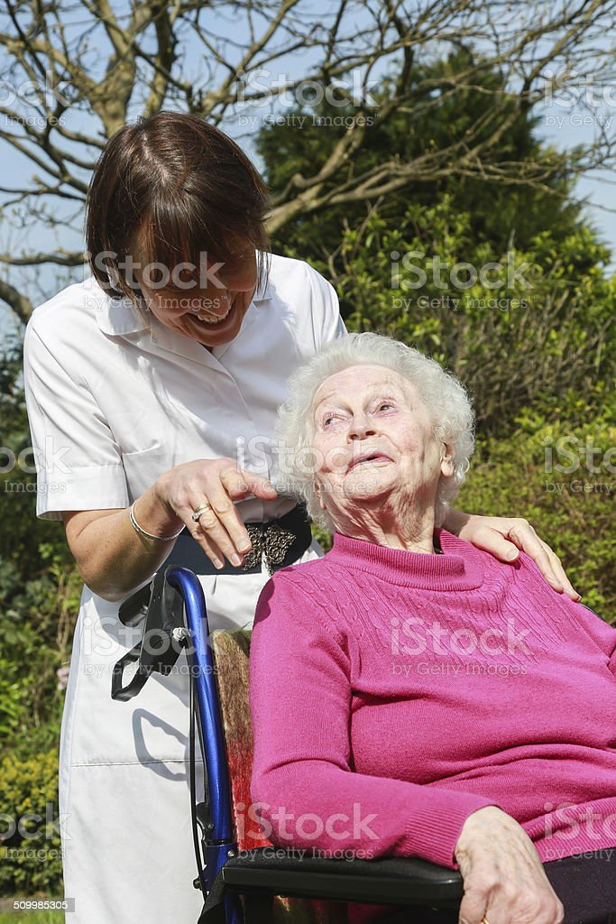 Care worker nurse providing company to an elderly woman. stock photo