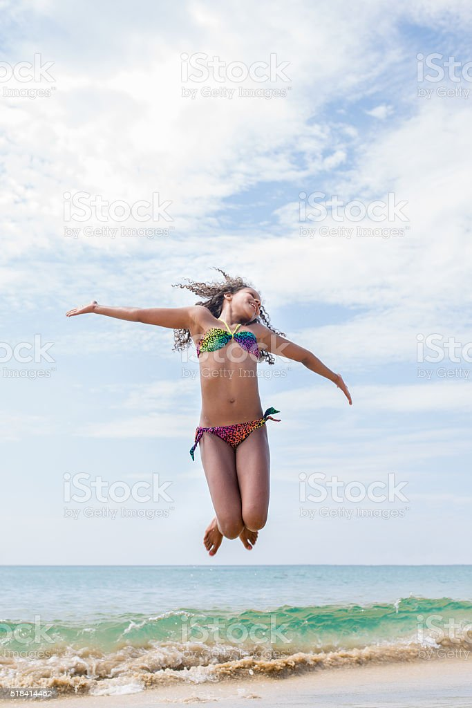 Carefree African American teenage girl jumping on the beach. stock photo