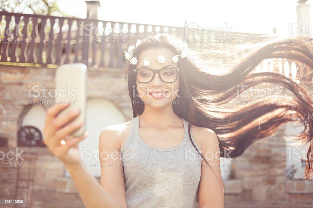 Carefree boho woman making selfie outdoors stock photo