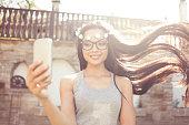 Carefree boho woman making selfie outdoors
