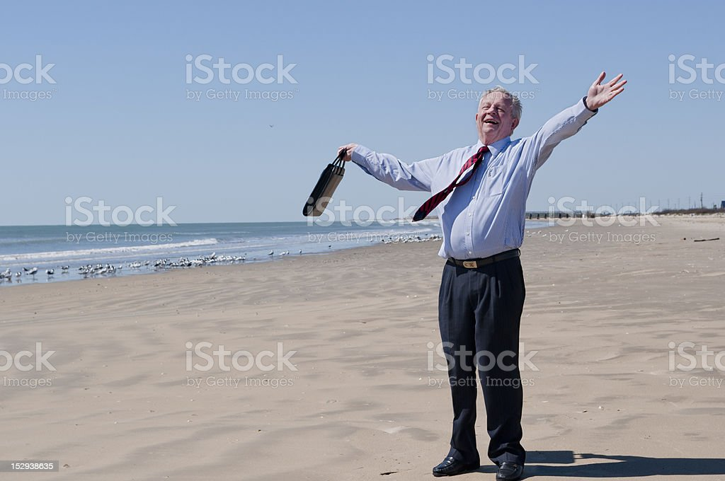 Carefree Businessman Enjoying A Sunny Day At Deserted Beach stock photo