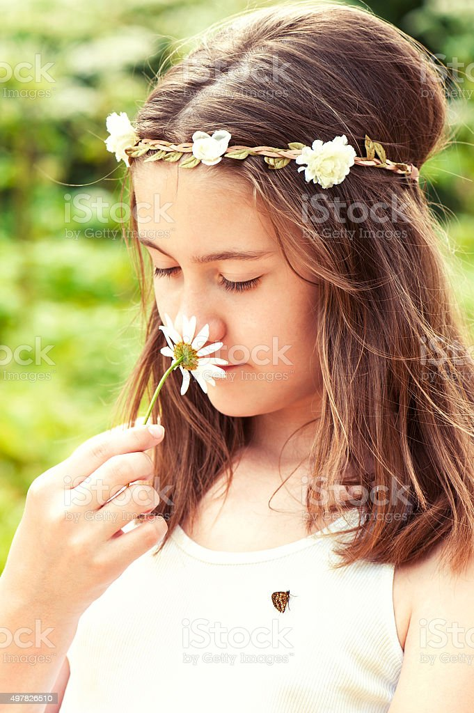 Carefree childhood. Girl with butterfly smelling camomile . stock photo