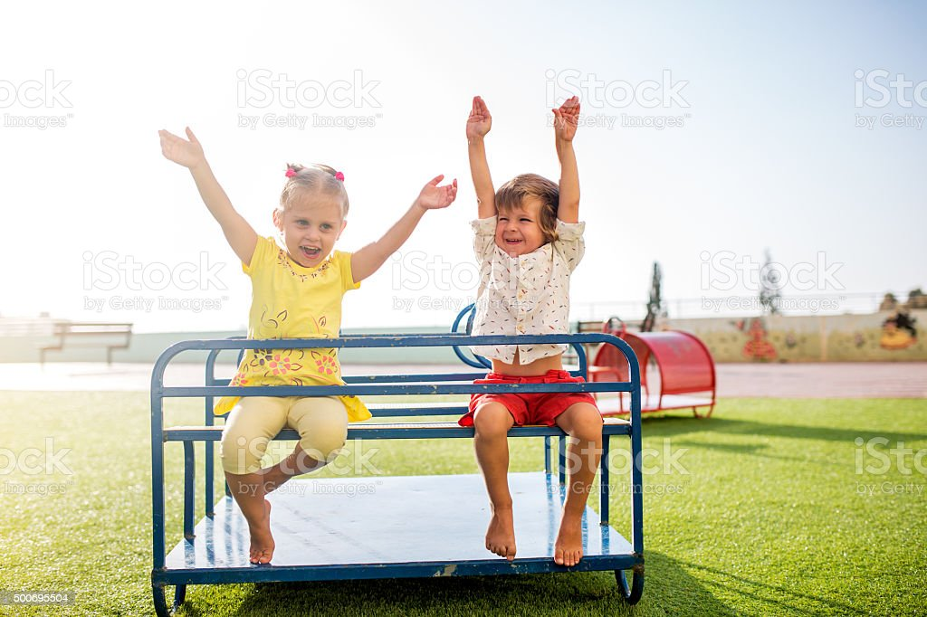 Carefree children having fun on a playground. stock photo
