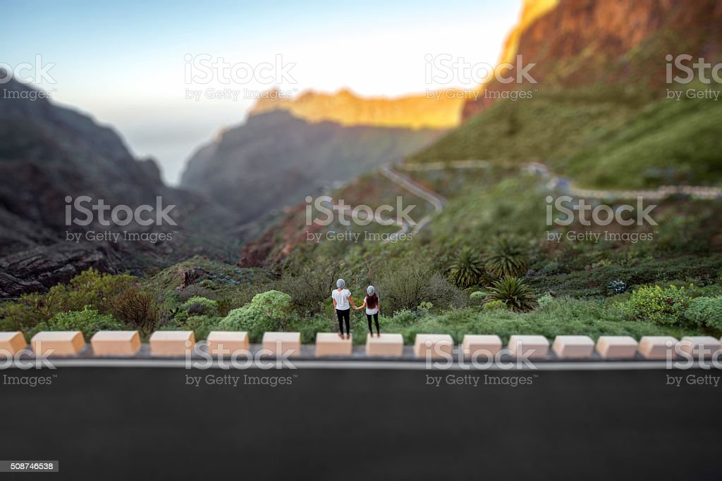 Carefree couple standing on the mountain roadside stock photo