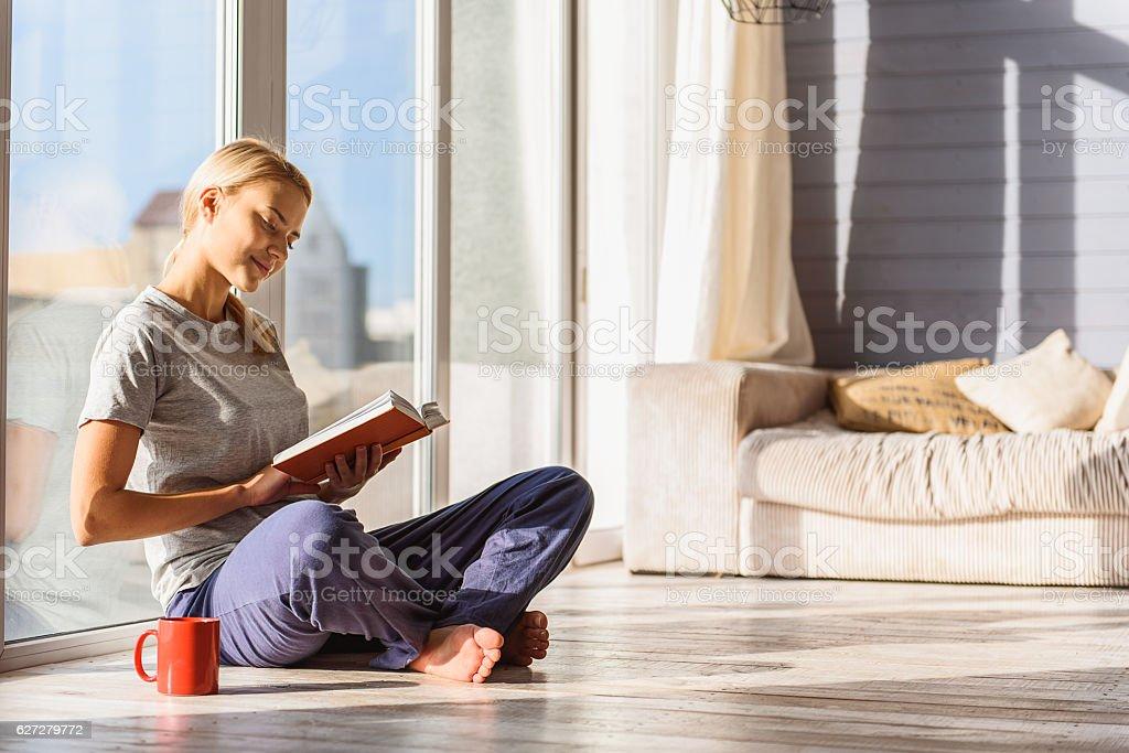 Carefree girl enjoying favorite literature stock photo
