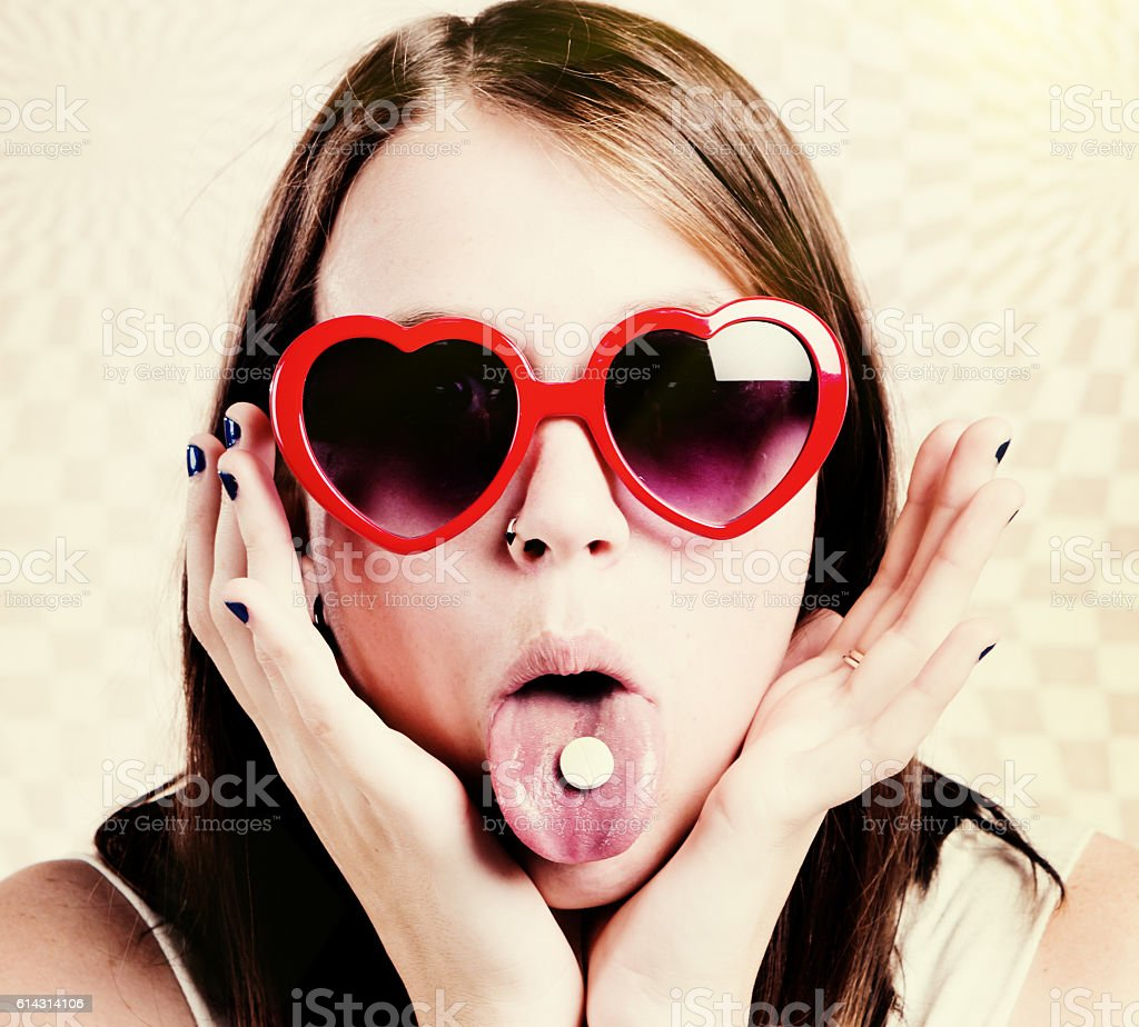 Carefree girl in sunglasses  taking tablet, possibly LSD or Ecstasy stock photo