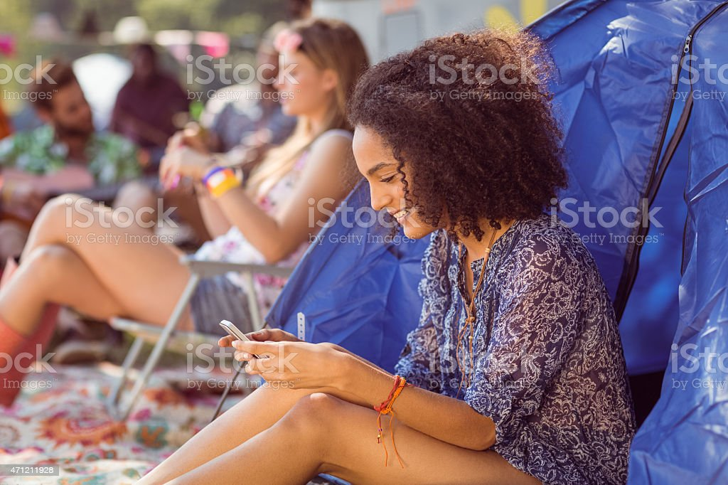 Carefree hipster sending text message stock photo