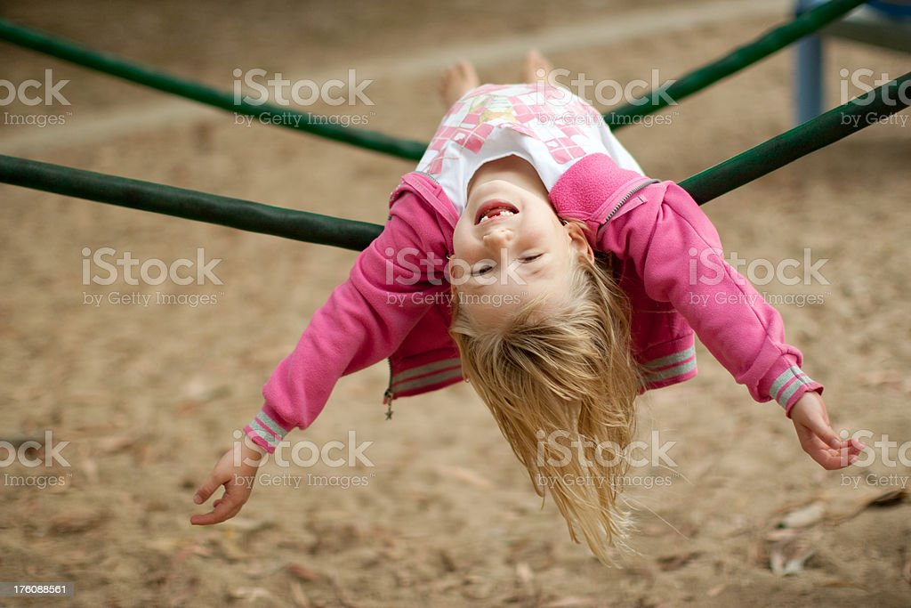Carefree little girl upside down on playground equipment royalty-free stock photo