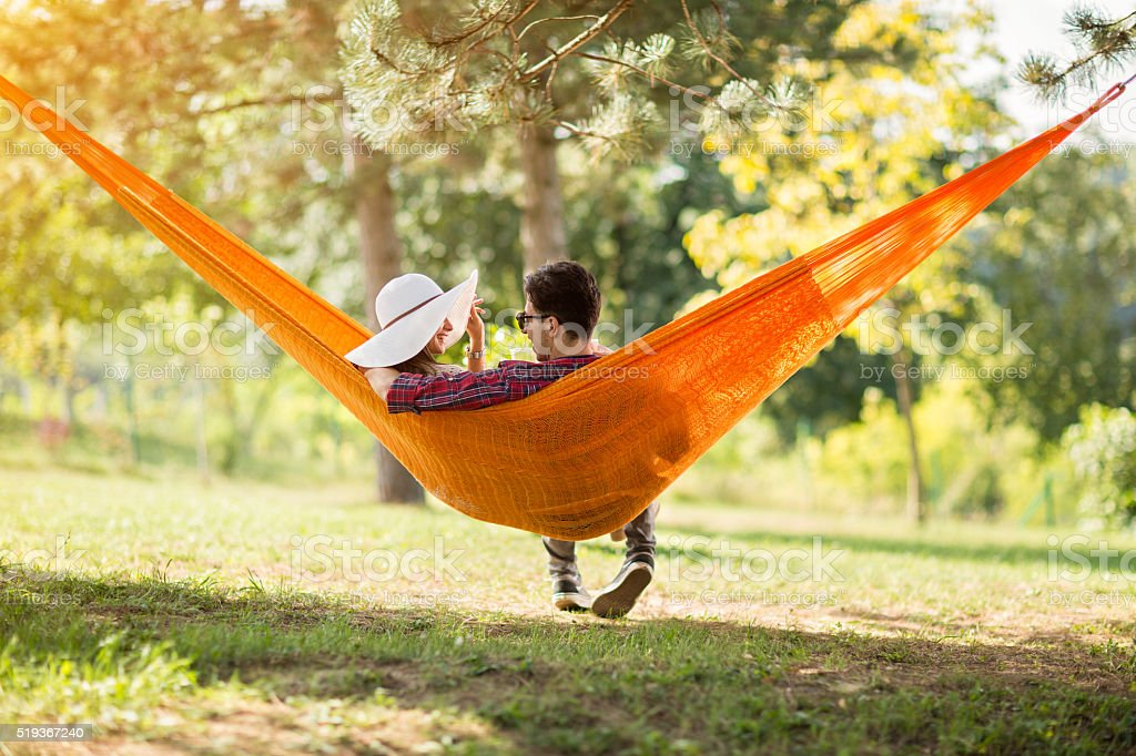 Carefree male and female in hammock from back stock photo