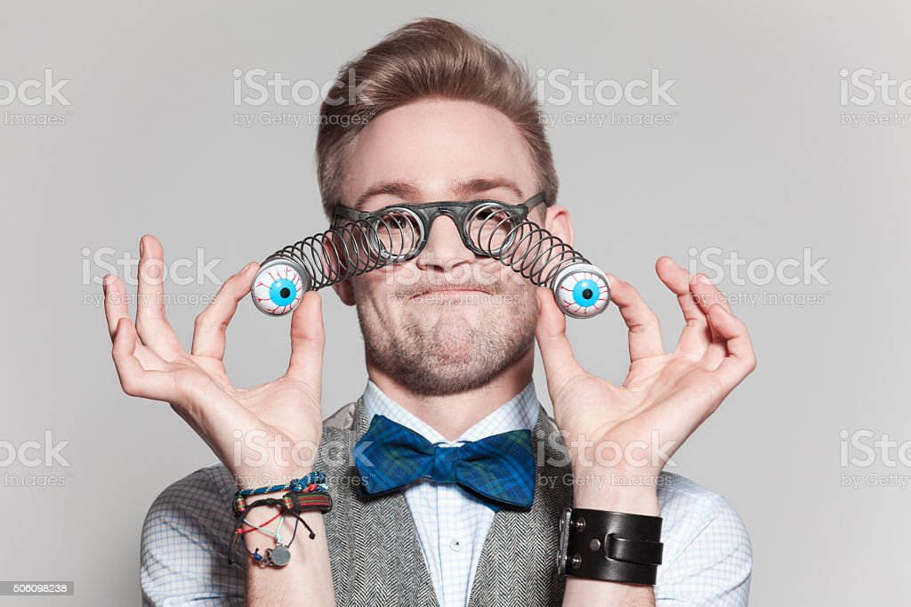 Carefree man wearing tweed vest, bow tie and funny glasses stock photo