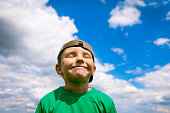 Carefree, smiling boy in the blue sky and white clouds.