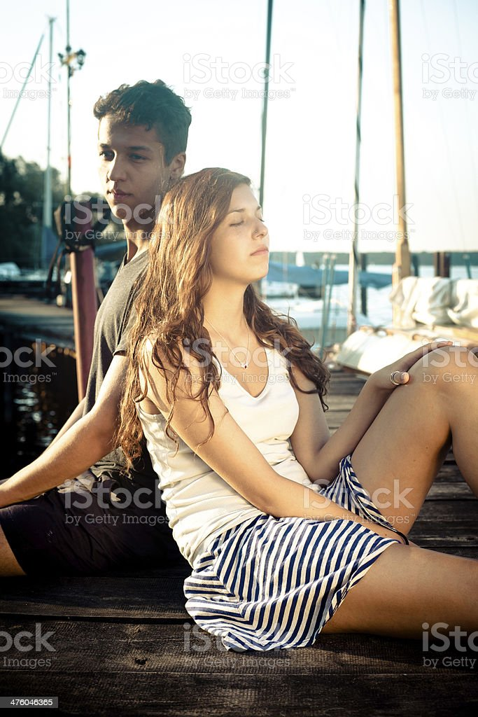 carefree summer day: cute teenage couple sitting on jetty royalty-free stock photo