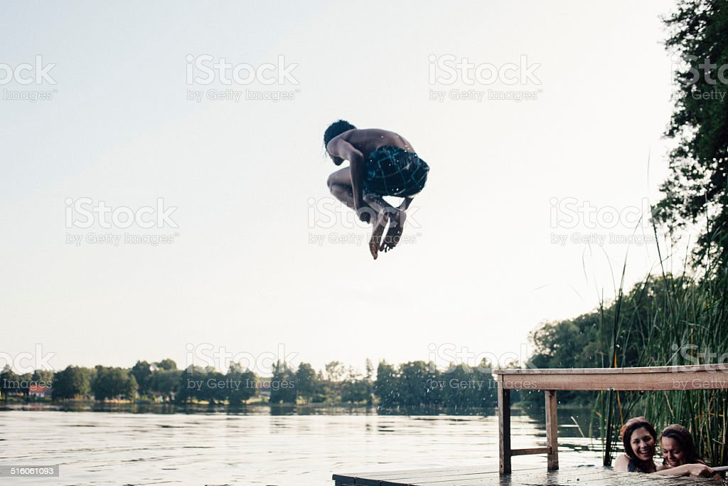 carefree summer day: teenager jumps into a lake stock photo