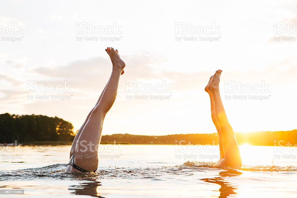 carefree summer day: two teenage girls making handstand in lake stock photo