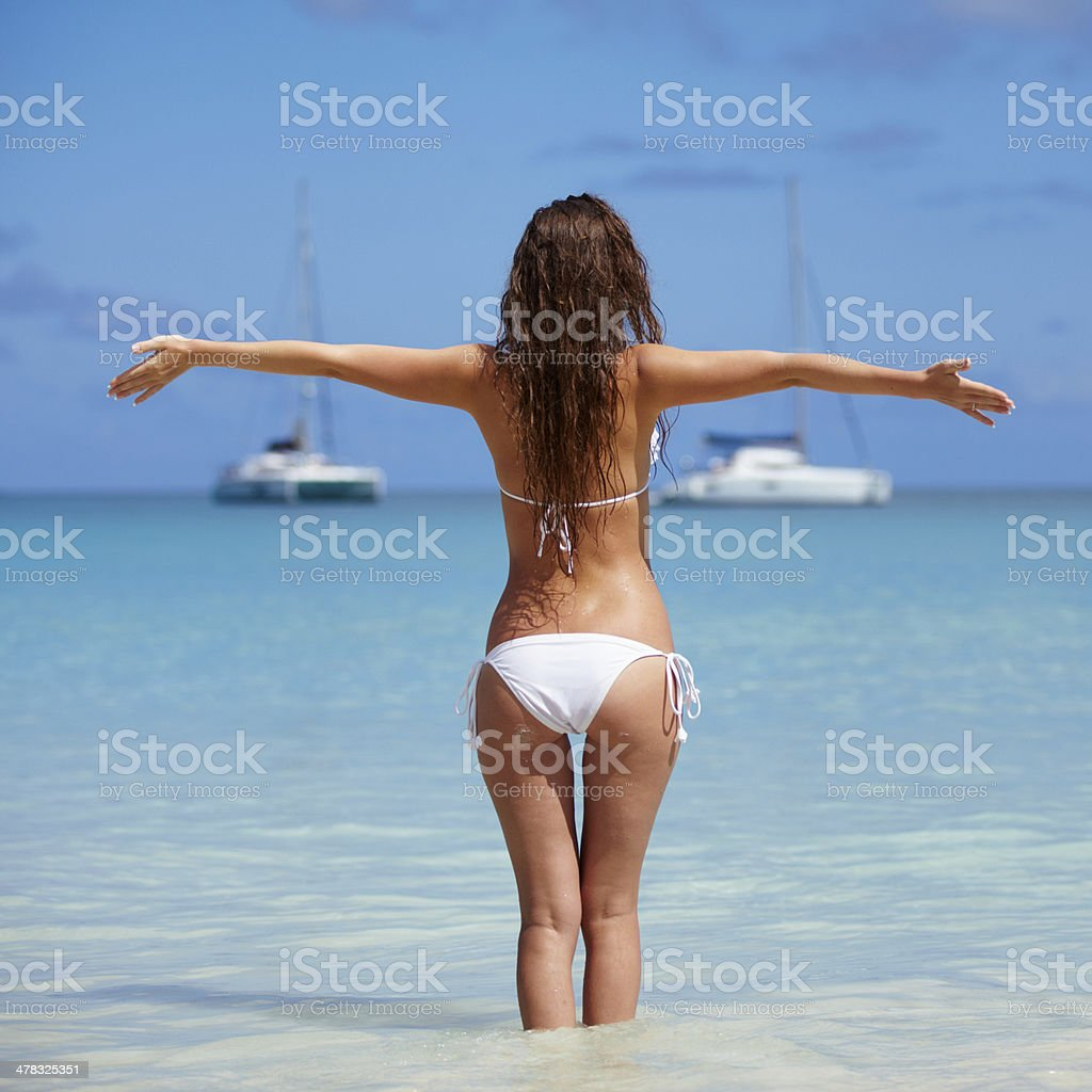 Carefree woman enjoying with arms outstretched at beach royalty-free stock photo