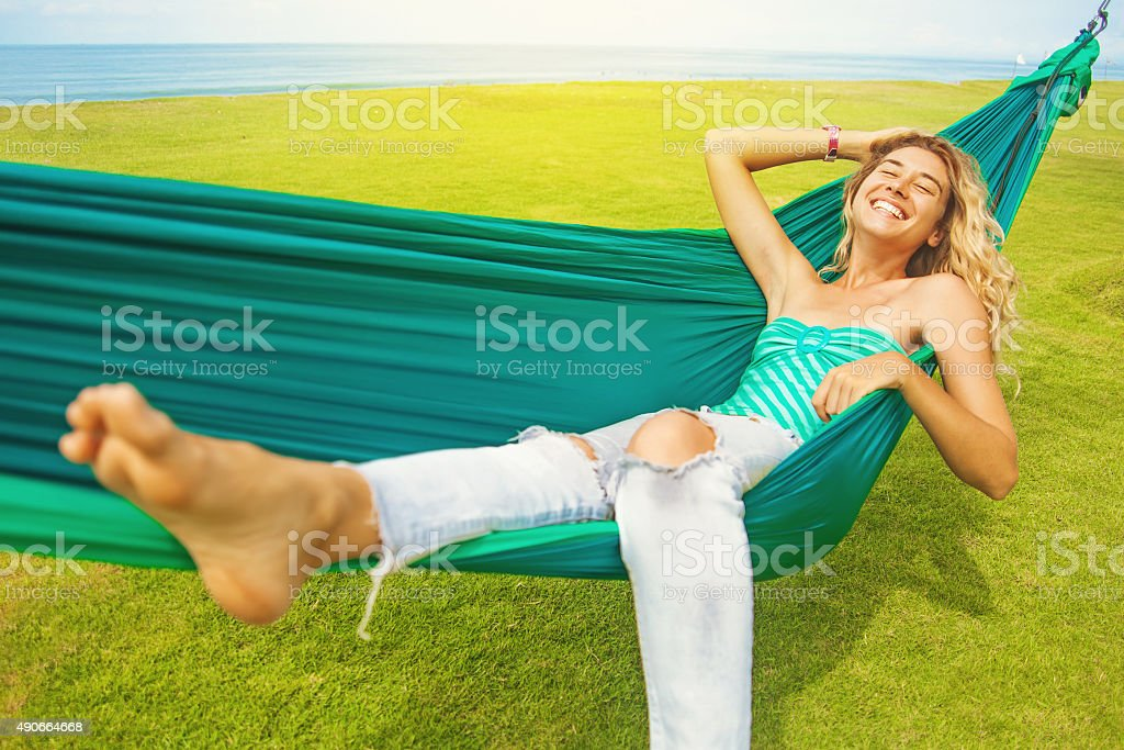 carefree woman relaxing in a hammock stock photo