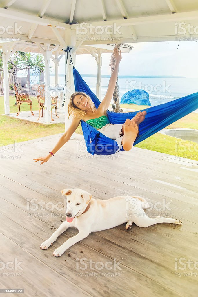 carefree woman relaxing in a hammock with dog stock photo