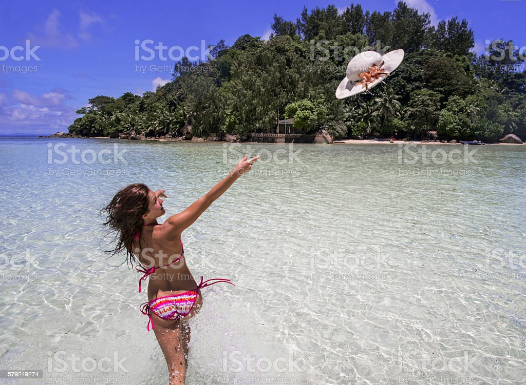 Carefree woman throwing sun hat while running through sea. stock photo